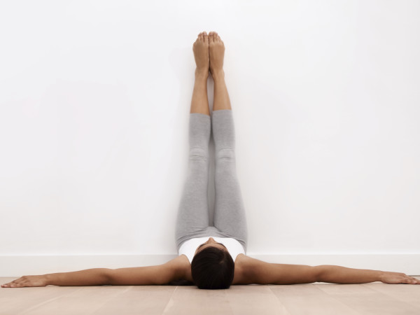 A young woman stretching against a wall before exercise